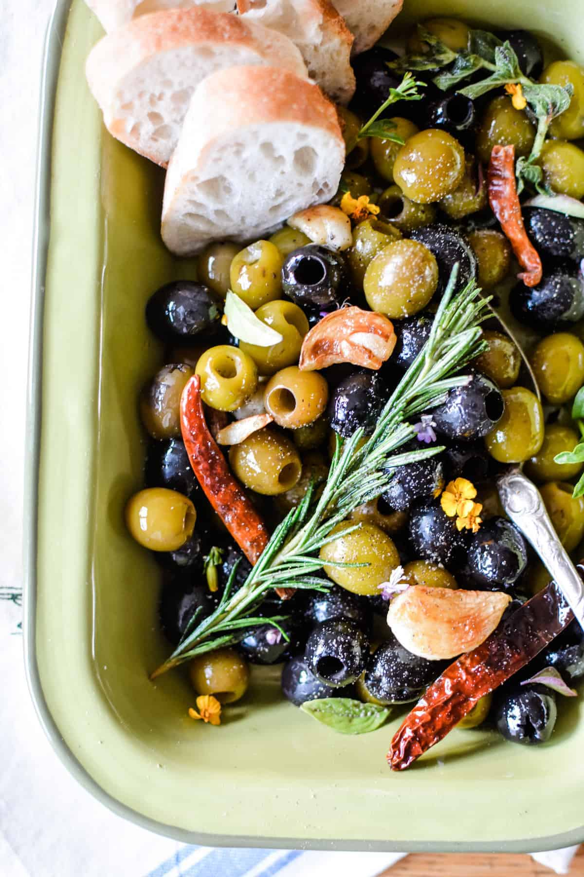 A green dish with black and green olives in it and a sprig of rosemary on the top with roasted garlic and dried arbol chiles.
