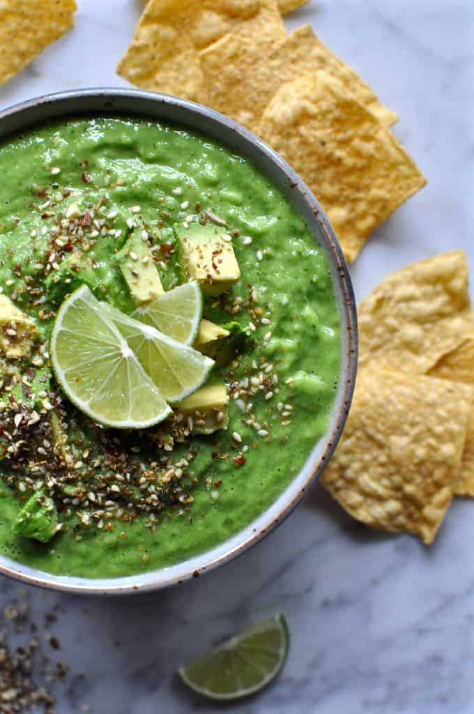 Green tomatillo salsa verde in a bowl on a marble table with seeds on top and lime wedges. Several tortilla chips are near by.