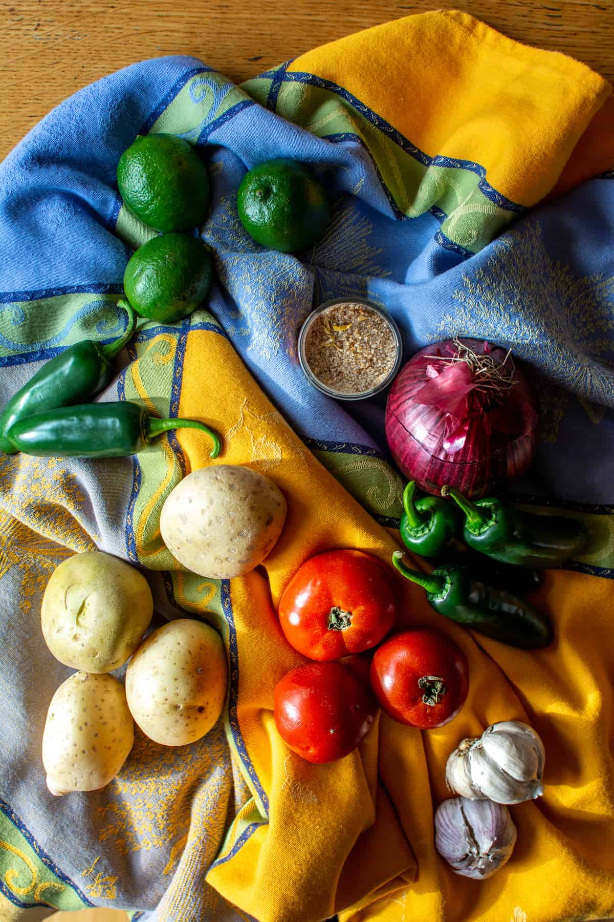 Ingredients to make Papas con Chile including potatoes, jalapeños, limes, salt, red onion, garlic, and tomatoes spread on a cloth.