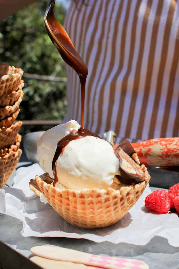 Two scoops of vanilla ice cream in a waffle dish with someone pouring caramel sauce from a spoon over the top.