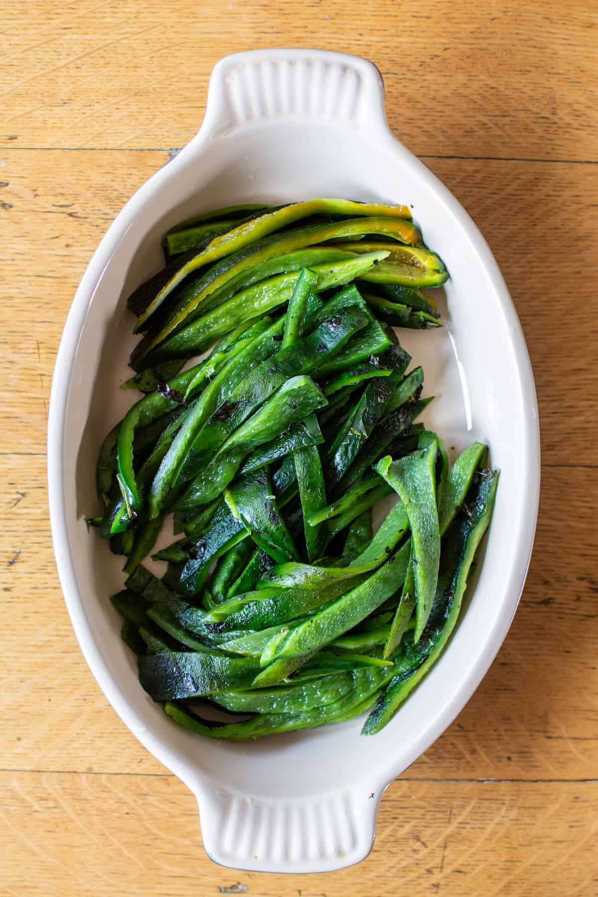 A dish of roasted poblano peppers cut into strips sitting on a wood table.