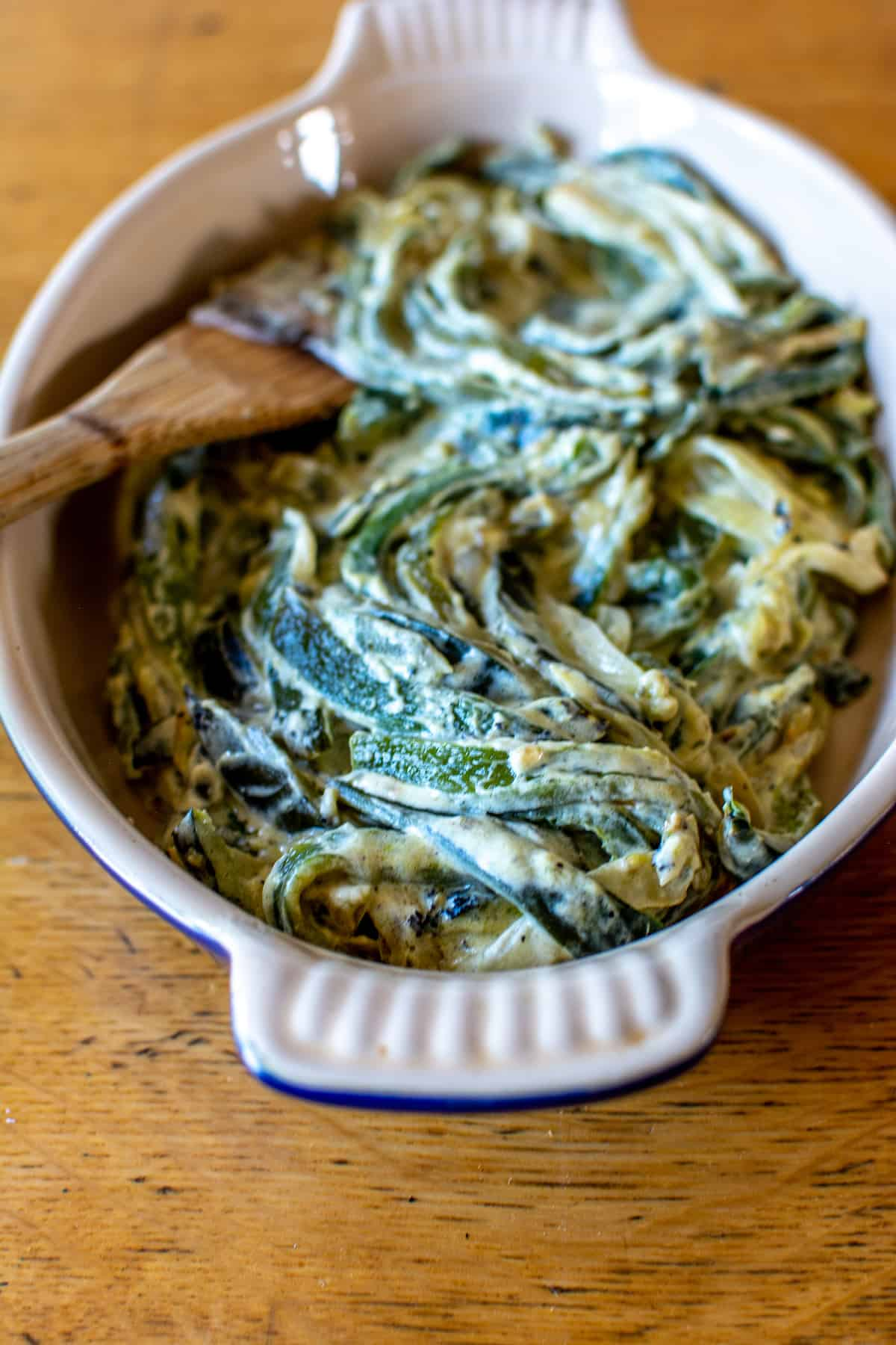 A close up of Rajas con Crema or roasted strips of poblano pepper with onions and cream.