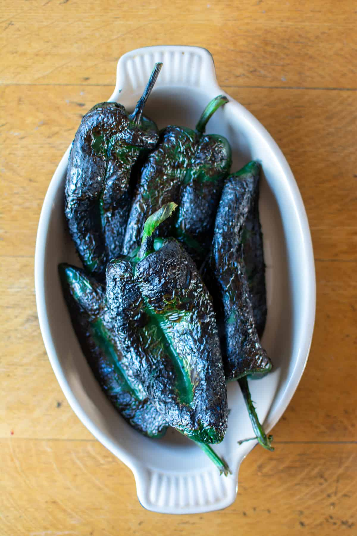 A dish of charred and blackened poblano peppers sitting in a dish on a wood table.