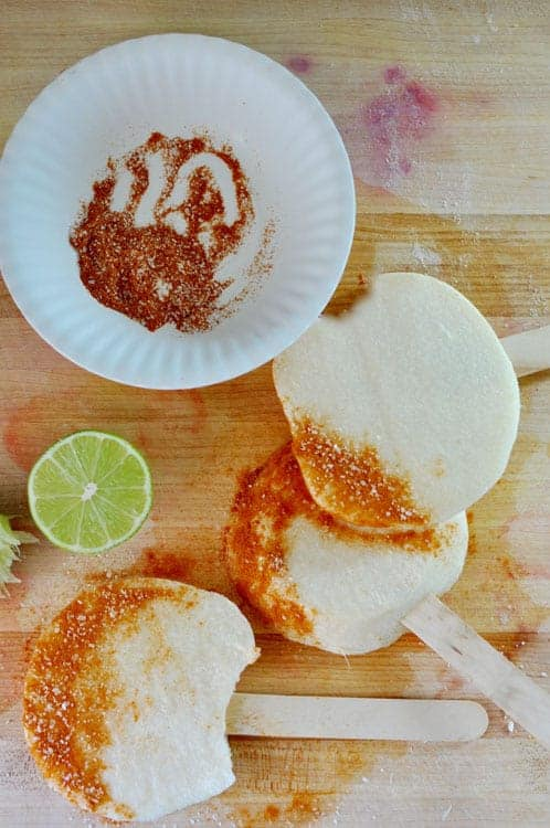 Three round jicama pieces on wooden sticks with the ends covered in chili powder and salt on a wood cutting board next to half of a lime.
