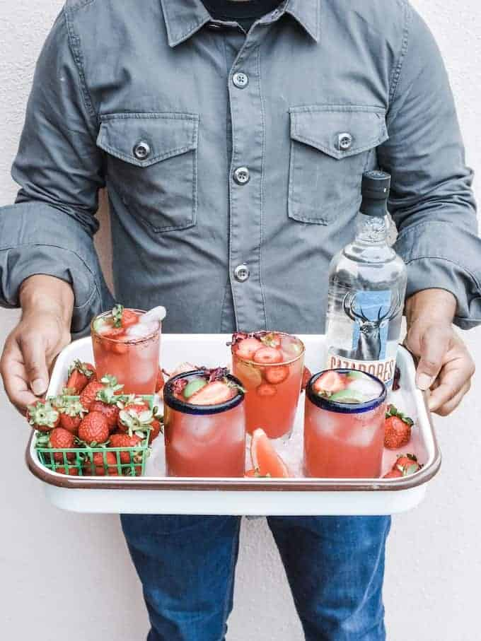 Man holding a white tray that has 4 glasses of pink Paloma cocktails with strawberries and a bottle of tequila and grapefruit wedges.