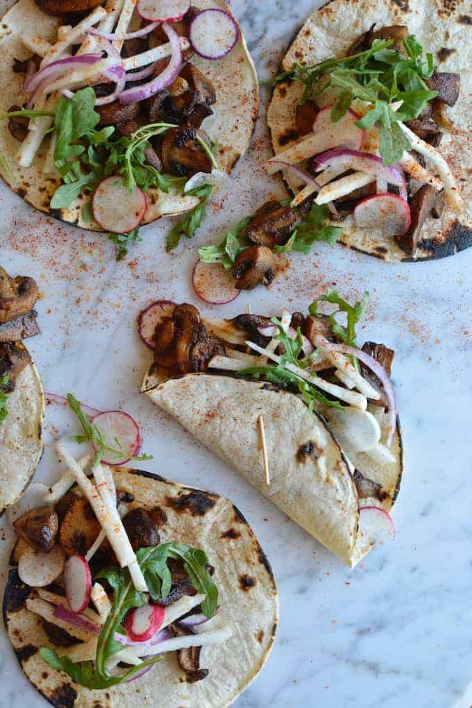 Several mushroom tacos sitting on a marble counter with jicama salad on top and chili powder sprinkled over them.