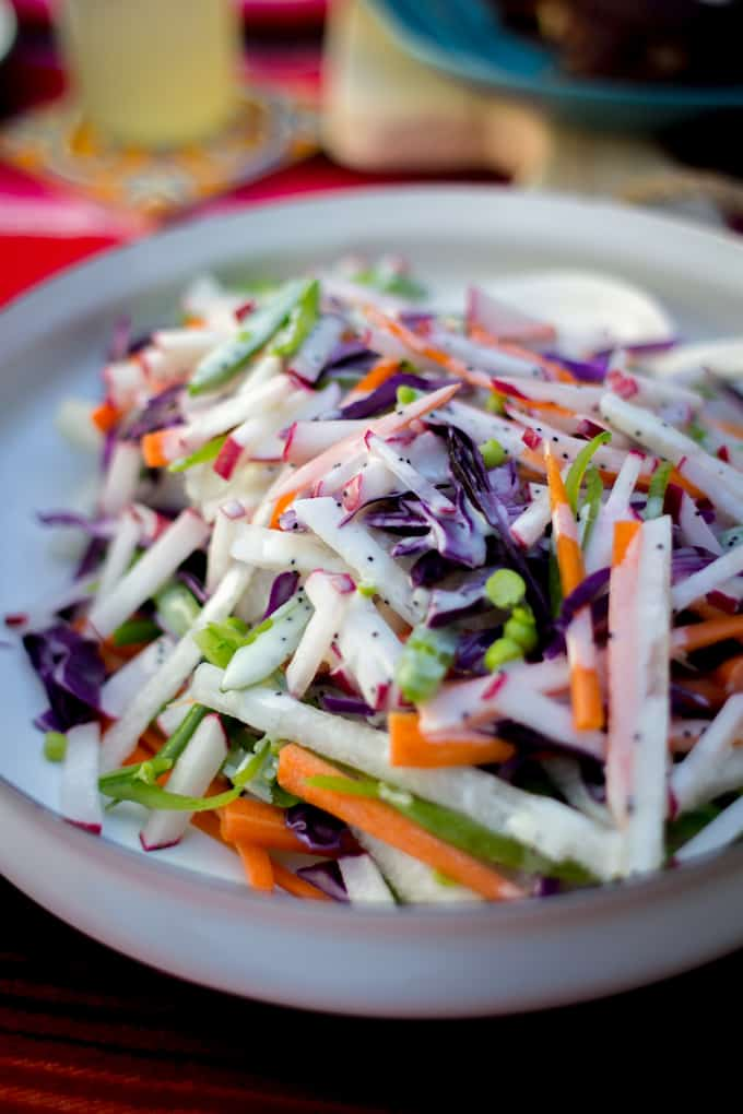 A white bowl filled with matchstick cut jicama, red cabbage, carrots, and sugar snap peas in a poppy seed dressing.