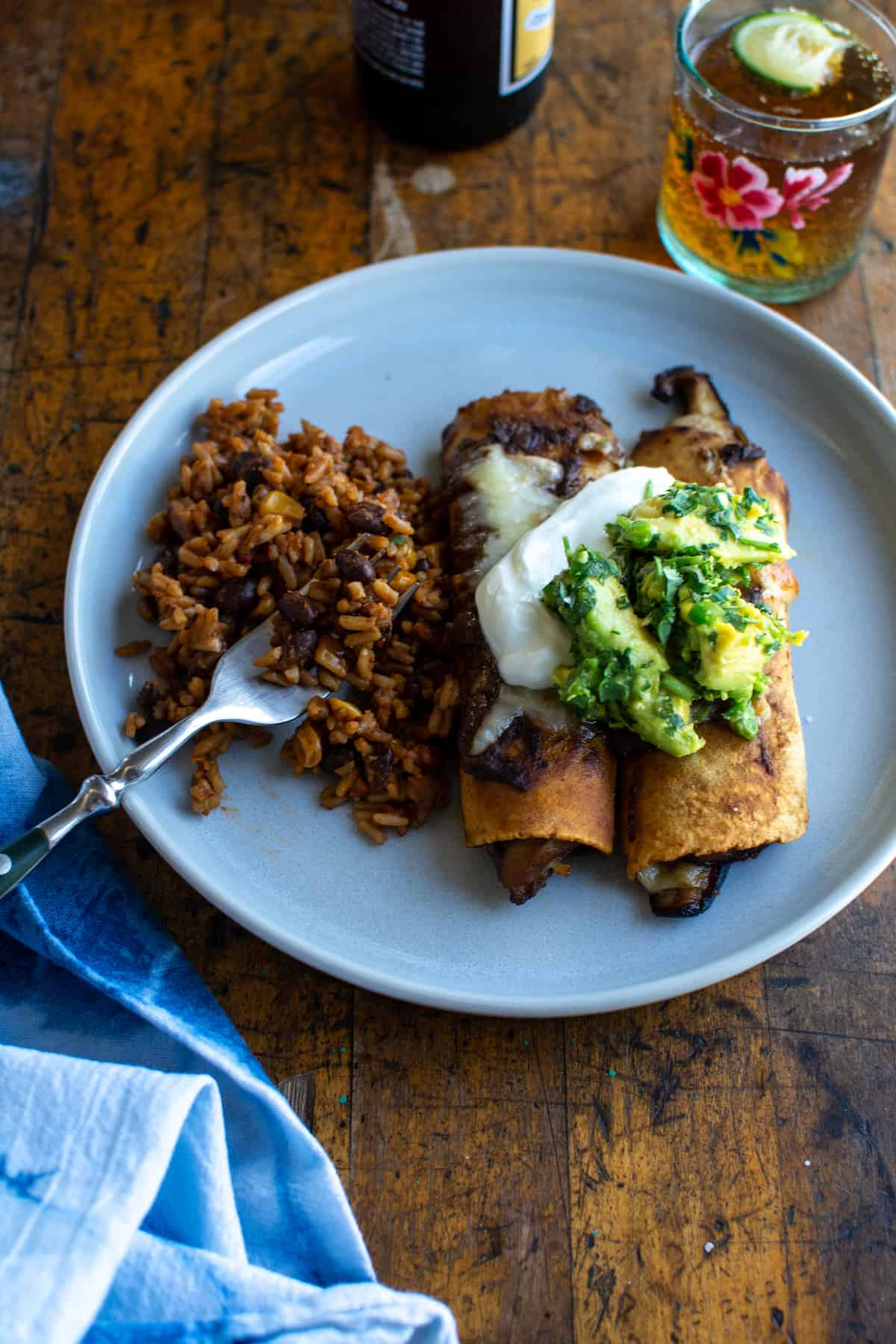 Two mushroom enchiladas sitting on a white plate with guacamole and sour cream on top with rice on the side and a glass behind it.