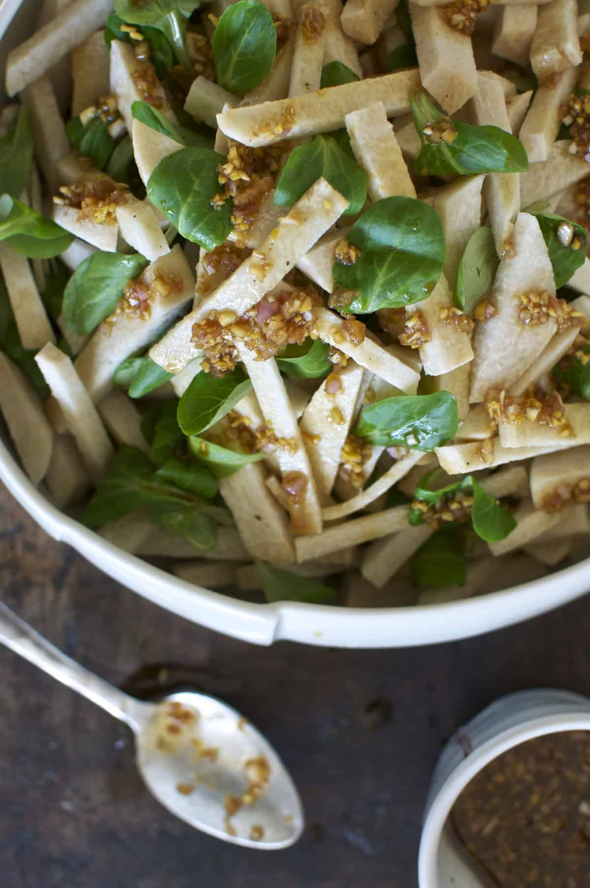 A white bowl with sticks of jicama and watercress leaves in the bowl with ginger dressing drizzled on top.