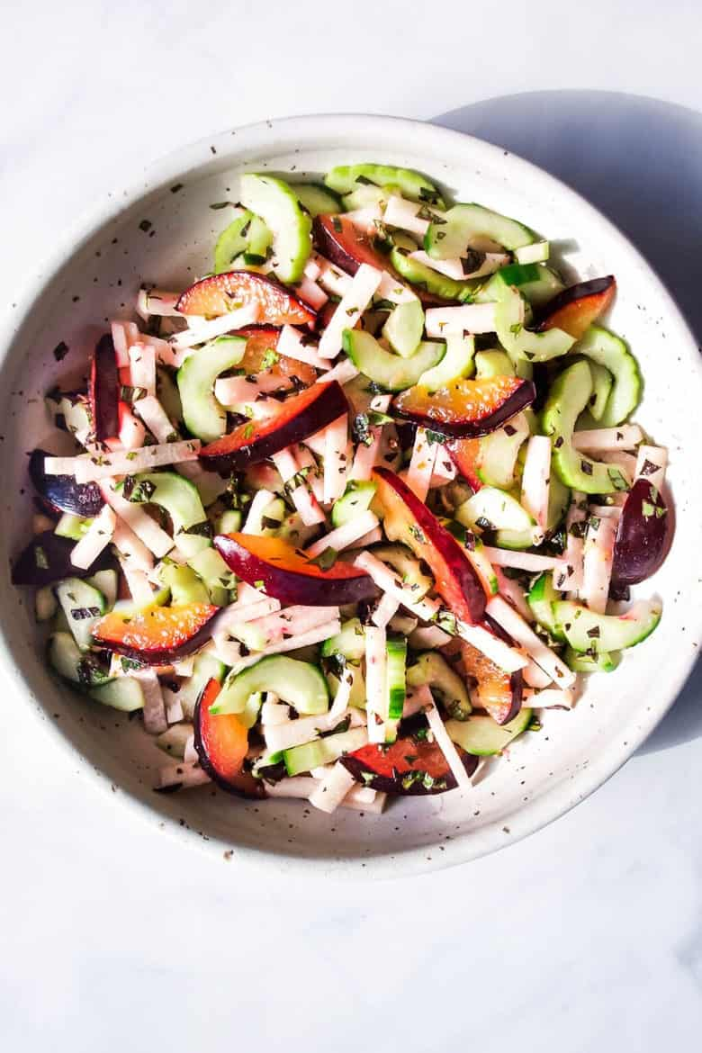 A white bowl with speckles that has a jicama salad with cucumbers, plums, jicama, and herbs.