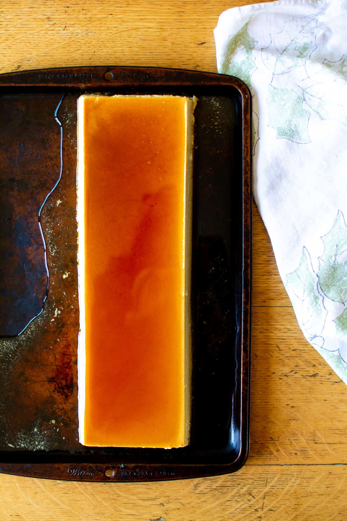 A rectangular flan on a baking sheet with a white towel near by sitting on a wood table.