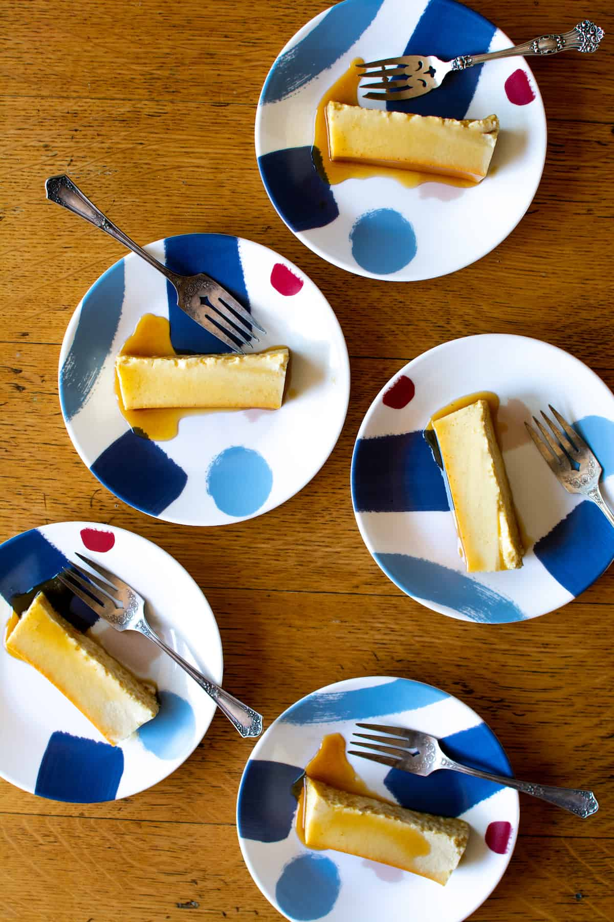 5 blue and white dessert plates with pieces of flan on them and forks on each plate.