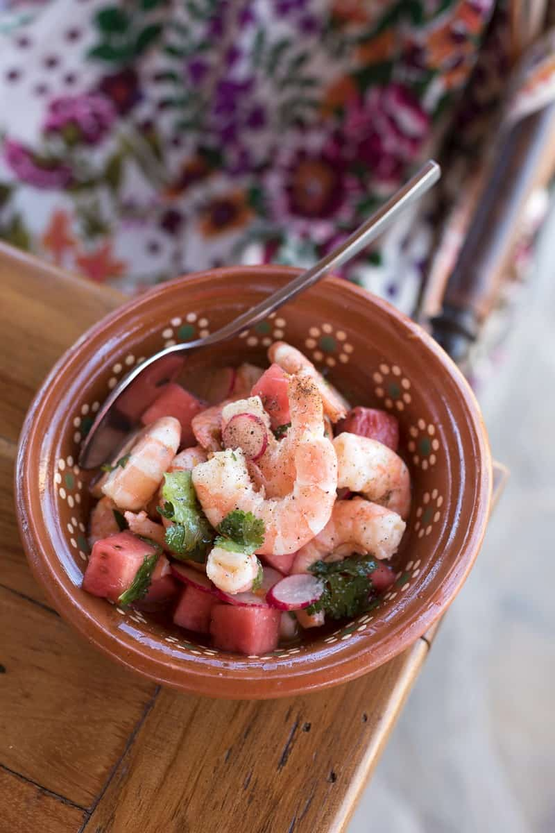 A small brown bowl with shrimp, watermelon, and jicama and sliced radishes along with some herbs in it. Sitting on a wood table.