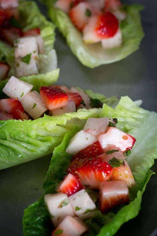 Strawberry and jicama diced in a lettuce cups with chopped herbs on top.