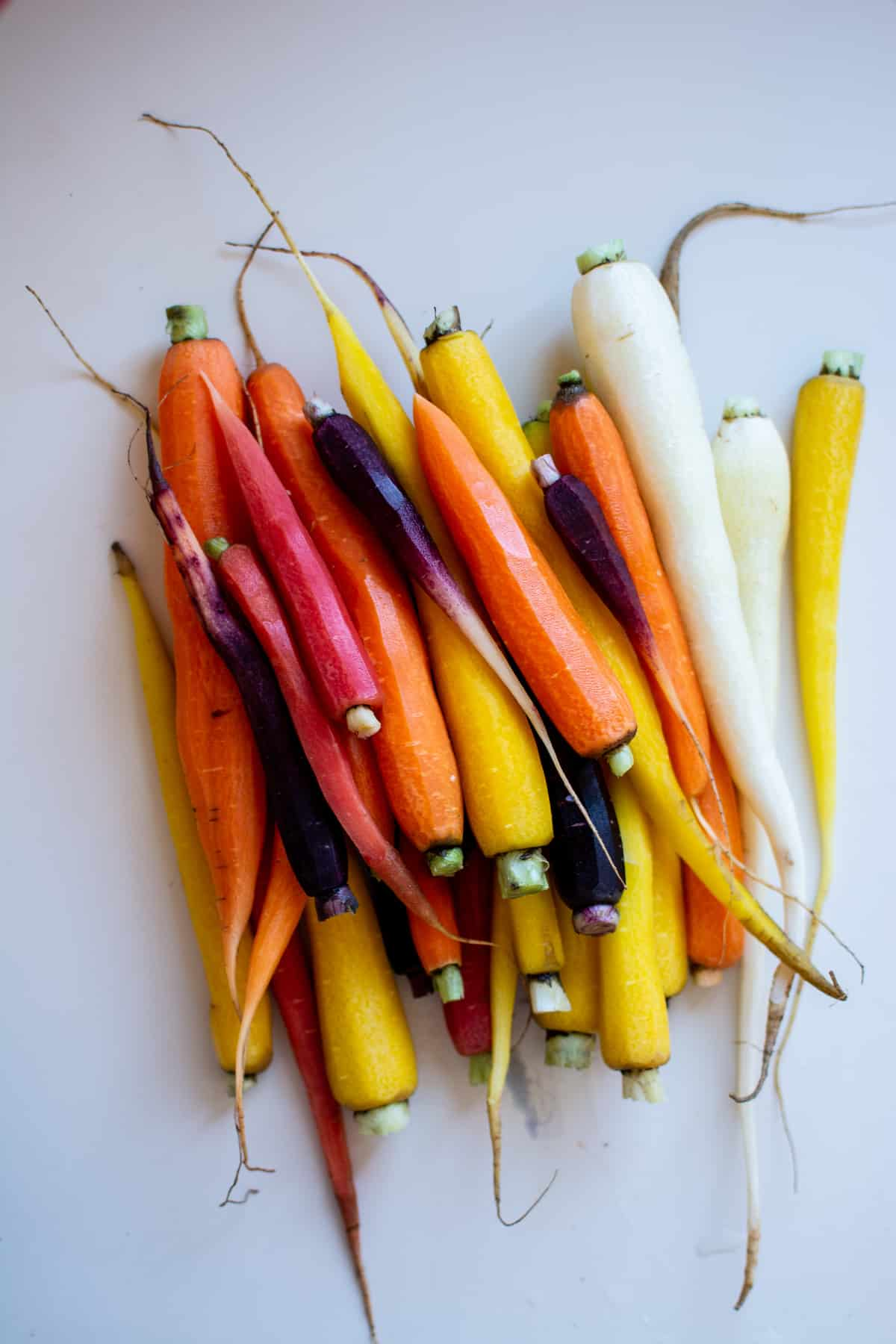 A pile of peeled rainbow carrots sitting on a white surface.