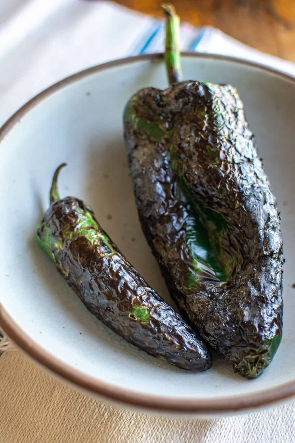 A jalapeño and a poblano pepper that have been charred sitting in a white bowl on a white towel on a wood table.