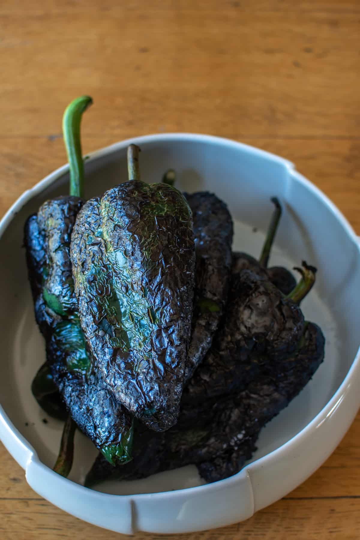 Several charred Chile Rellenos in a white bowl sitting on a wood table.