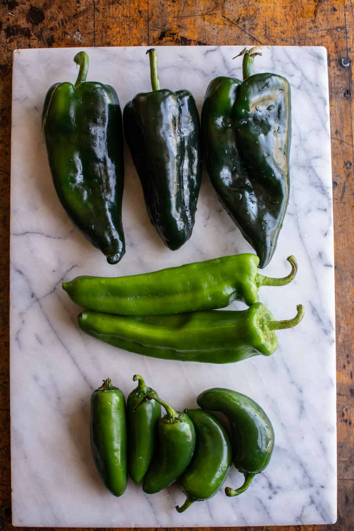 Poblano peppers, Anaheim chiles, and jalapeño peppers in rows on a marble cutting board that's sitting on a wood table.
