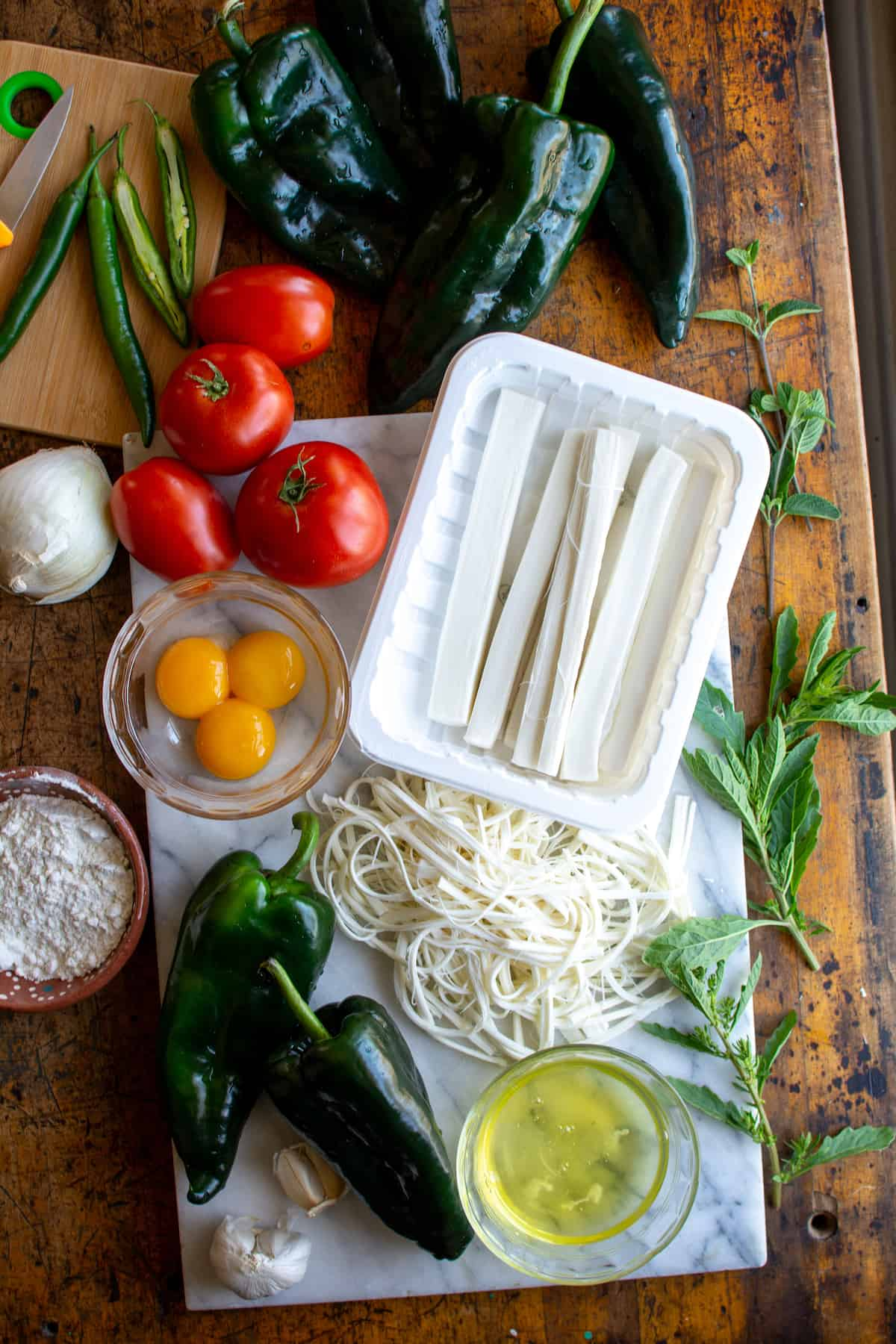 The ingredients for Chile Rellenos on a wood table including poblano peppers, Oaxaca cheese, tomatoes, serranos, and eggs.