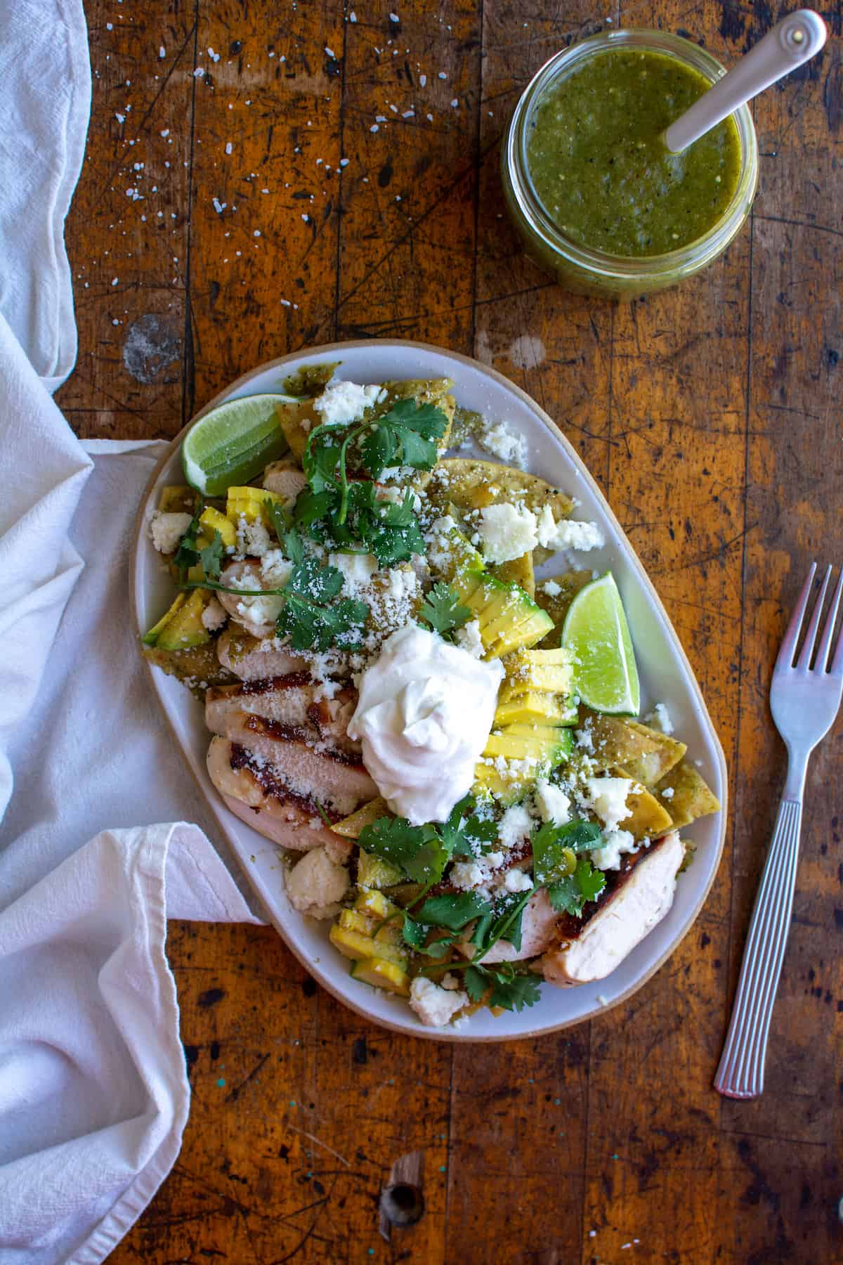 A plate of chilaquiles sitting on a wood table with a jar of salsa verde next to it.